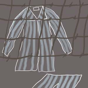 set of striped pajamas behind a barbed wire fence