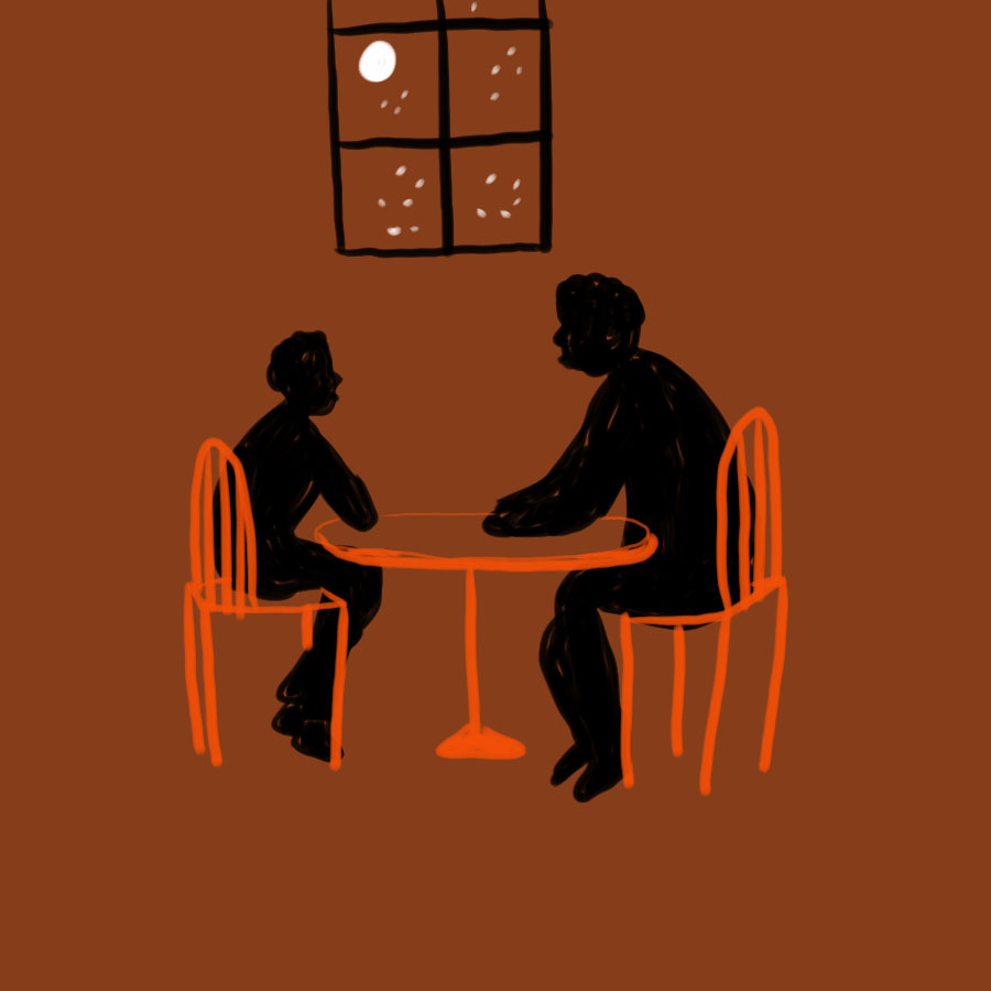 two people, one older and one younger, sit facing each other at a table with a window in the background